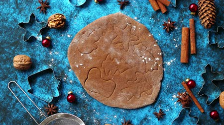 Christmas baking concept. Gingerbread dough with different cutter shapes and spices on sides. Top view on blue rustic background. Wideo