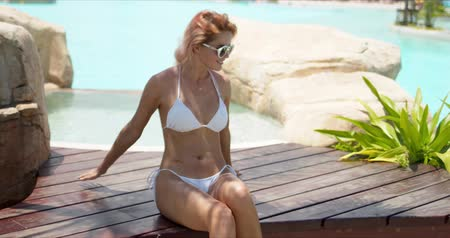 Tanned pleasant woman in sunglasses and white bikini sitting on wooden ground decorated with stones and plants nearby swimming pool in windy day