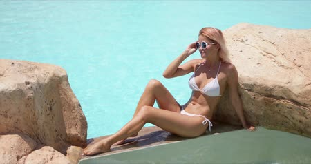 Side view of tanned slim woman in sunglasses and white swimwear leaning on stone sitting on poolside and looking away