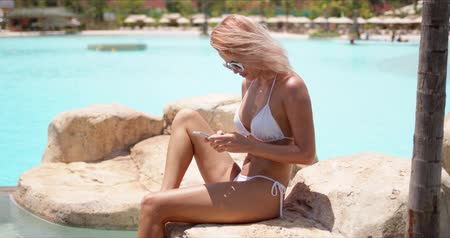Side view of cheerful woman in white swimsuit and round sunglasses surfing mobile phone sitting on stone surrounded swimming pool in bright day