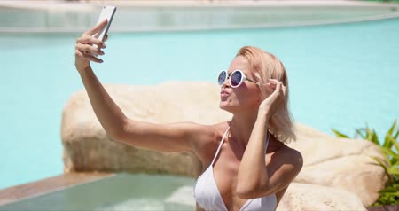 Joyful cheerful woman in white bikini and sunglasses taking selfie on mobile phone showing v sign and sticking tongue out spending time at poolside