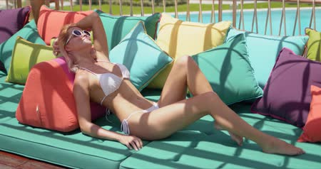 Smiling relaxed woman in white swimsuit and sunglasses having rest on soft sofa with colorful pillows and looking at camera on resort