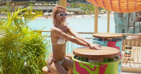 чувственный : Pleasant woman with slim figure in white bikini waiting for order at round table on wooden terrace in resort in bright day