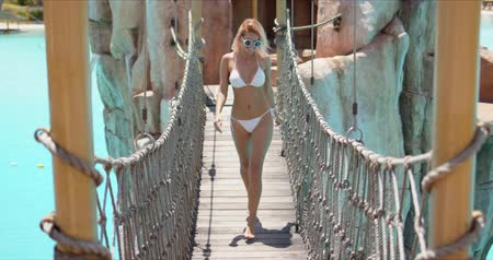 Cheerful sportive woman in white swimsuit running on suspension bridge with rope fence above serene water in resort pool