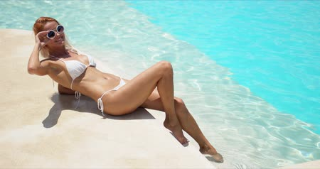 From above tanned pleasant woman in white bikini closing eyes and enjoying sunlight while lying on stone steps of resort pool Wideo
