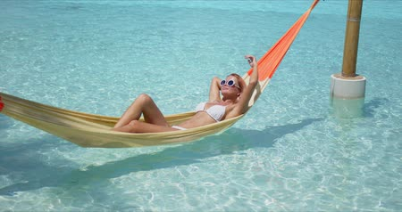 Side view of young tanned female in bikini and sunglasses enjoying summer holidays while lying on hammock over large pool in luxury resort 動画素材