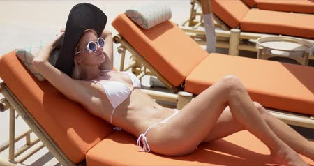 sunhat : Side view of attractive stylish female in wide brimmed hat and sunglasses wearing white bikini relaxing on deckchair at poolside