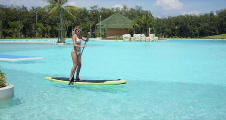 Side view of slim tanned female in bikini standing on paddle board in large swimming pool while spending summer holidays in luxury tropical resort Wideo