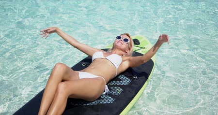 Attractive tanned female in white bikini and fashionable sunglasses lying on paddle board in swimming pool with crystal water in tropical resort Wideo