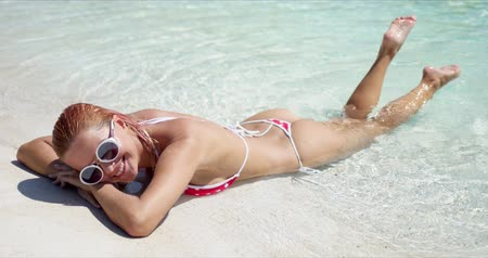 Delighted young female in bikini and shades smiling and swinging legs in clean sea water, while lying on sandy shore on sunny day during summer vacation