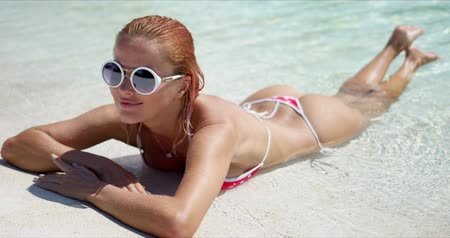 Cheerful young female in sunglasses and swimwear smiling and looking at camera while lying in clean sea water on sunny day on sandy beach
