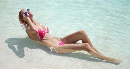 Side view of glad slim woman in bikini and sunglasses smiling and resting in transparent sea water on sunny summer day on resort