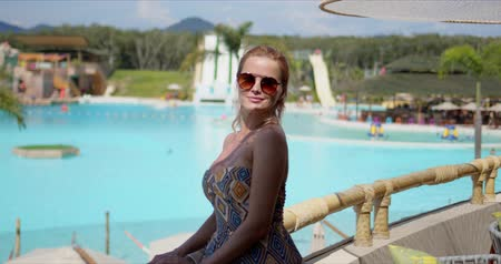 Optimistic woman in ornamental dress smiling and looking away while standing on hotel terrace against large swimming pool on sunny day on resort Wideo