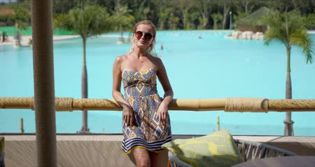 delighted : Delighted lady in summer dress smiling and looking at camera while leaning on terrace railing against swimming pool while resting on resort on sunny day