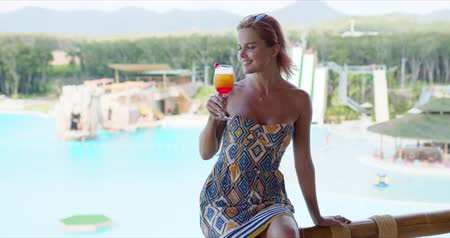 Cheerful stylish female with glass of fruit cocktail smiling and looking away while sitting on balcony railing on blurred background of swimming pool on resort Wideo