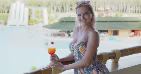 Side view of optimistic woman with fruit cocktail smiling and looking at camera while standing near raining on terrace on blurred background of swimming pool 動画素材