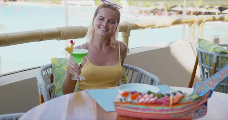 Happy female with glass of green beverage smiling and looking away while sitting at table on restaurant terrace during vacation on tropical resort