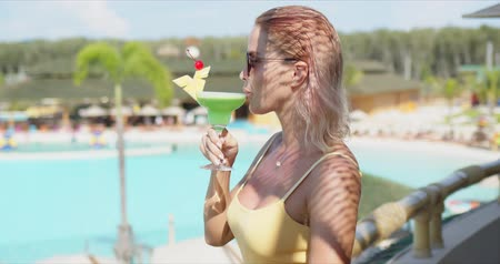 Side view of woman in sunglasses and yellow top smiling and enjoying green cocktail while standing on hotel balcony blurred background of swimming pool