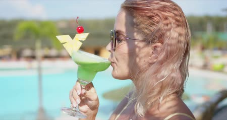 delighted : Side view of blond woman with closed eyes sipping green beverage while standing on blurred background of swimming pool on resort