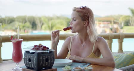 восхищенный : Glad lady smiling and looking away while sitting at table on restaurant terrace and enjoying tasty snack during vacation on tropical resort Стоковые видеозаписи