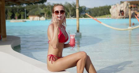 delighted : Side view of delighted woman in swimwear smiling and looking at camera while drinking fresh fruit cocktail near swimming pool with clean water on resort