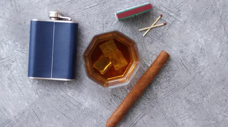 maltês : Glass of whiskey with ice, big cuban cigar, matches and hip flask placed on gray stone table.