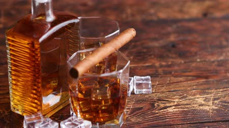 Bottle of whiskey with two glasses and cuban cigar placed on rustic wooden table.