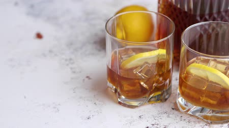 ice cube : Whiskey sour drink with lemon in glass on stone rustical background. Two glasses filled with ice and carafe Stock Footage
