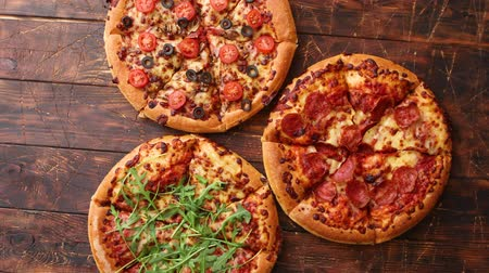 Thick american style homemade on fluffy dough pizzas with various ingredients placed on a brown wooden table.