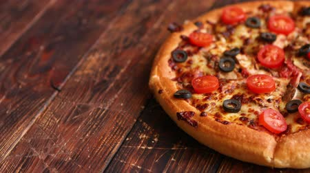 calabresa : Pizza pepperoni with mozzarella cheese, tomato sauce, salami, black olives, cherry tomatoes. American style pizza on brown rusty wooden table background.