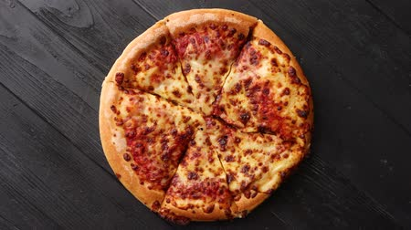 Fluffy dough, pepperoni pizza in american style placed on rusty old black wooden table. Top view with copy space for text.