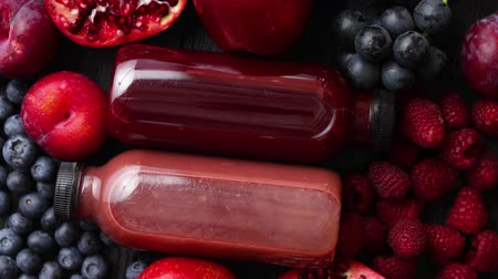 amoras : Mix of fresh red and black fruits. With botteled fresh juices. Placed on black wooden table.