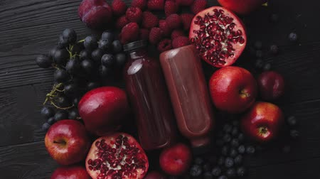 Various fresh red, purple black fruits. Mix of fruits and bottled juices on black background. Selection of healthy vegetarian food, detox or diet concept. With copy space.