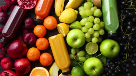 kivi : Various healthy fruits and vegetables formed in rainbow style composition. Placed on black wooden table. With bottles on fresh squeezed juice. Stok Video