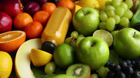 blackberry : Various healthy fruits and vegetables formed in rainbow style composition. Placed on black wooden table. With bottles on fresh squeezed juice. Stock Footage