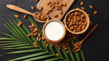 kalsiyum : Close up of Almonds in wooden bowl and almond milk. Placed on black stone table. Palm leaf as a decoration. With copy space for text.