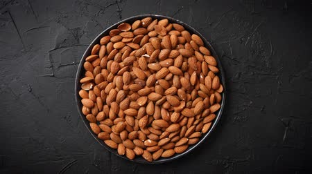 Whole almond nuts in black plate placed on black stone table. Healthy vegetarian snack. Copy space for text.