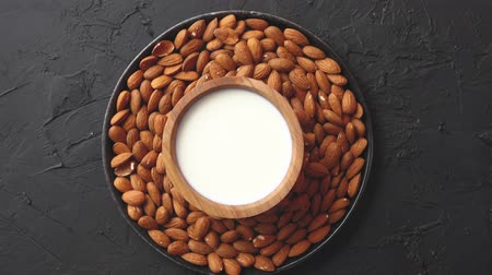 cálcio : Composition of almonds seeds and milk, placed on black stone background. Copy space for text.