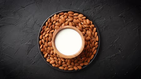 Composition of almonds seeds and milk, placed on black stone background. Copy space for text.