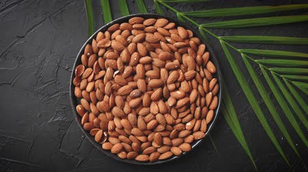 Composition of Whole almond nuts in black plate placed on black stone table. Green palm leaf as a decoration. Healthy vegetarian snack. Copy space for text.