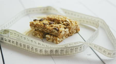 Homemade rustic granola bars with dried fruits on white wooden background. Fit concept with measure tape. Stock mozgókép