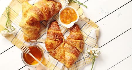 From above shot of delectable fresh croissants lying on checkered towel near bowl of yummy jam and jar of sweet honey on white lumber tabletop