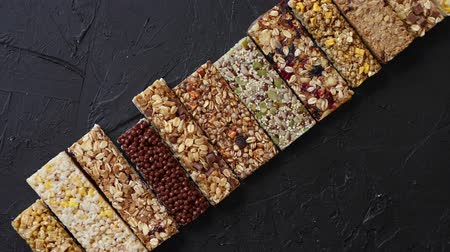 tartmak : Various healthy granola bars placed in a row on black stone table. Fitness concept. Dietary food. Top view with copy space. Stok Video