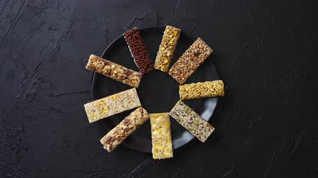 Different kind of granola fitness bars placed on black ceramic plate on a table. Healthy diet concept. Top view with copy space.