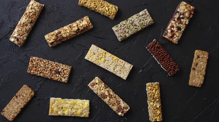 tartmak : Various taste and flavour granola fitness bars concept. Placed on black stone background. Top view. Stok Video