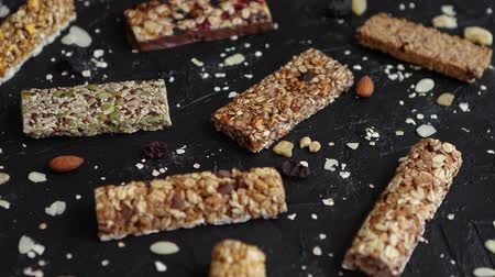 Mixed gluten free granola cereal energy bars. With dried fruits and nuts. Placed on black stone background. Healthy vegan super food. Fitness dieting snack for sporty lifestyle. Top view.
