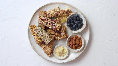 kepek : Mixed composition of energy nutrition bar, granola on ceramic plate over white background with copy space. Healthy breakfast. Top view, flat lay Stok Video