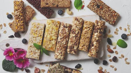 клюква : Homemade gluten free granola bars with mixed nuts, seeds, dried fruits on white stone background. Top view. Стоковые видеозаписи