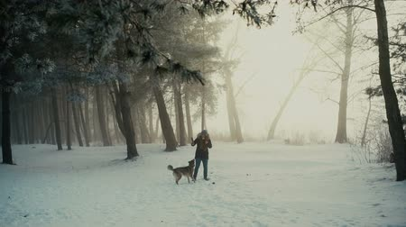 Happy girl playing with her dog on snow and having fun in winter forest