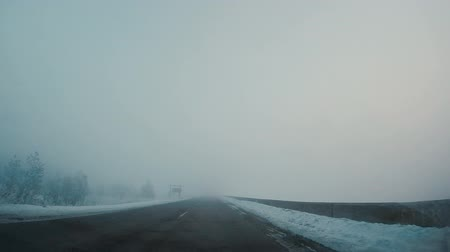 rural area : Driving car in winter in fog Stock Footage